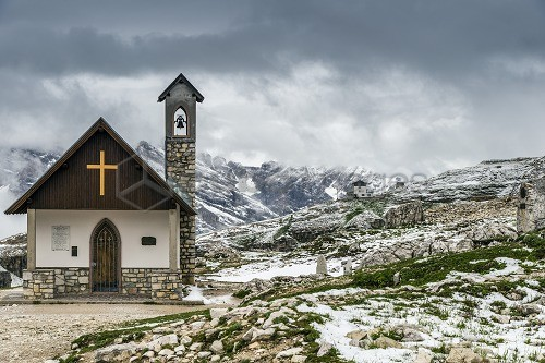 Small mountain church in the Dolomites after a summer snowfall, Cadore, Veneto, Italy