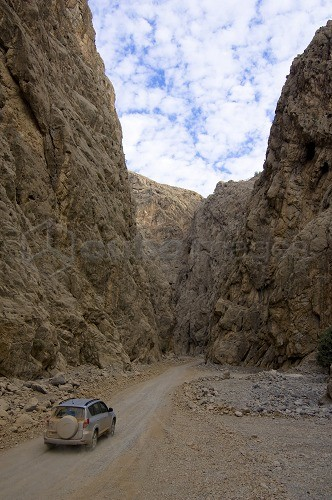 4x4 jeep driving through a canyon, dirt road, mountain landscape, Hajjar mountains, Musandam, Oman