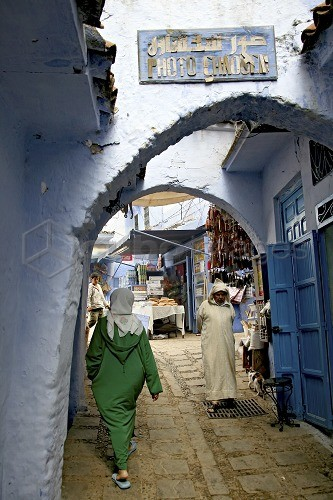 People in a narrow alley of Chefchaouen's medina, Chefchaouen, Morocco, Africa