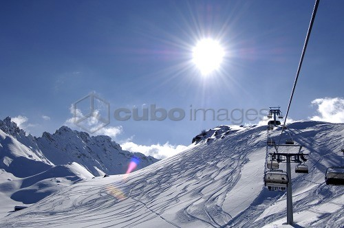 Chair lift in front of snow covered mountains in the sunlight, Dolomites, South Tyrol, Italy, Europe
