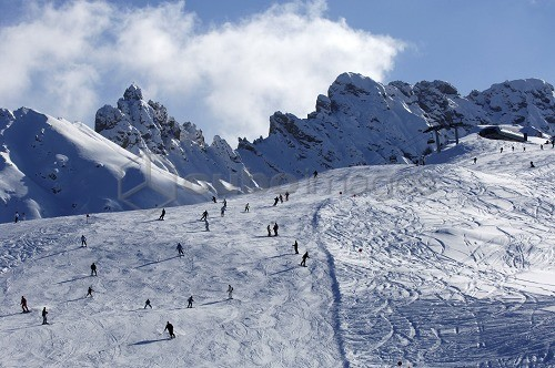 View at skiers on a ski slope under clouded sky, Alpe di Siusi, Dolomites, South Tyrol, Italy, Europe