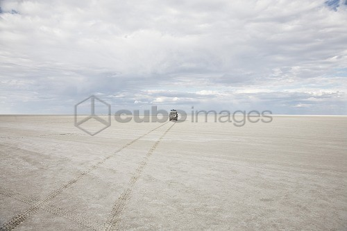 Off road car under clouded sky, Ntwetwe salt lake, Botswana, Africa