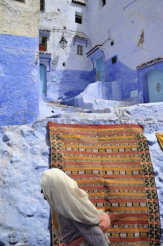 Old woman in front of a carpet and blue walls in a narrow alley at Chefchaouen, Riff mountains, Morocco, Africa