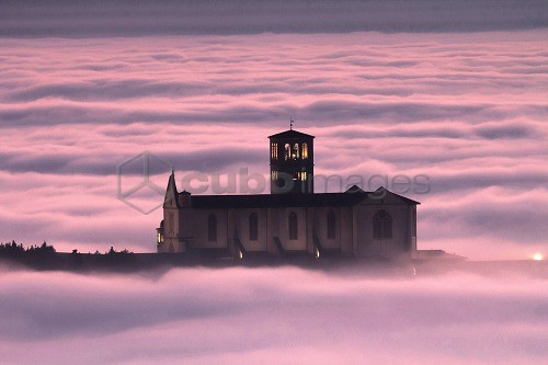 Basilica of St. Francis, at sunset with the city immersed in the fog, Assisi, Umbria, Italy, Europe