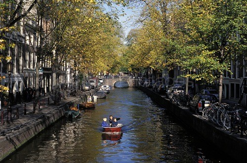 Small boat on tree-lined Oudezijds Achtenburg Wal canal in the autumn, Amsterdam, The Netherlands (Holland), Europe