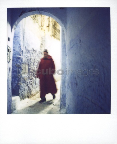 Polaroid of man wearing red djellaba walking through bluewashed archway, Chefchaouen, Morocco, North Africa, Africa