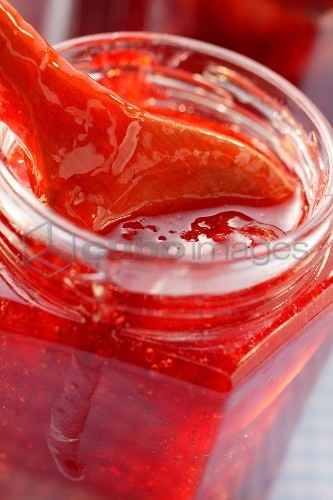 Strawberry jam in jar with wooden spoon