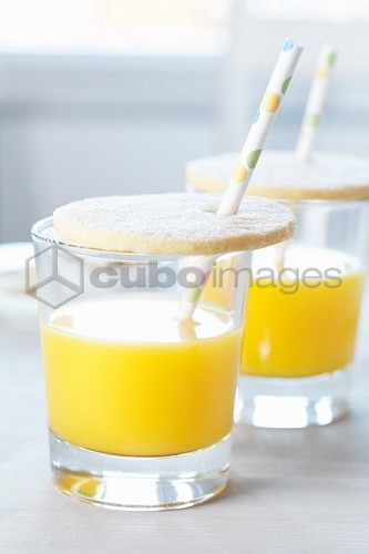 Glasses of orange juice with biscuit lids and drinking straws