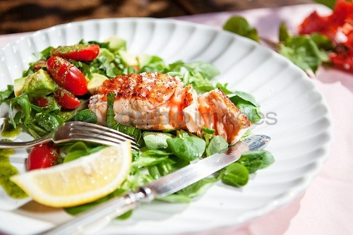 A salmon fillet on a bed of lamb's lettuce with tomatoes, avocado and pesto