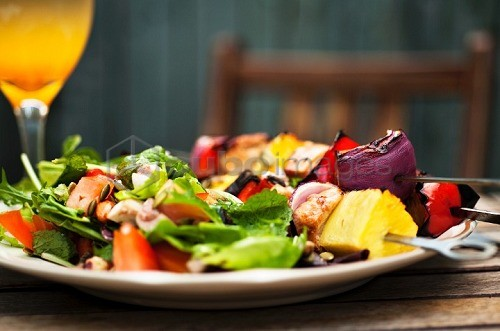Barbecued chicken kebabs with a side salad on a garden table