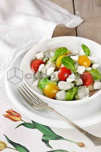 Spinach gnocchi with tomatoes, sheep's cheese and lamb's lettuce