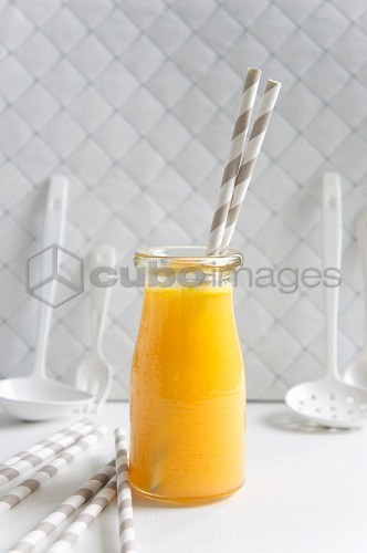 A bottle of orange juice with straws