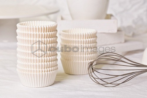 Stacks of muffin cases next to a whisk