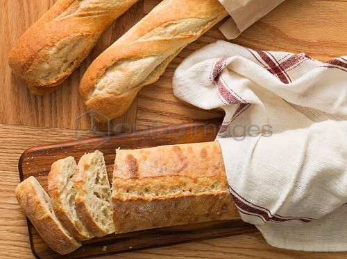 Freshly baked baguette with a tea towel on a chopping board