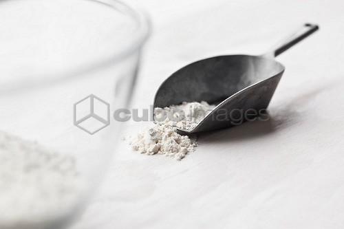 Flour in a metal scoop next to a bowl of flour