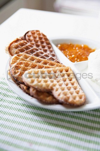 Heart-shaped waffles with vanilla ice cream and cloudberry jam