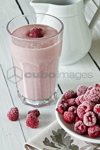 A raspberry smoothie and frozen raspberries