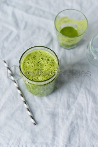 A green smoothie in a glass with striped straw