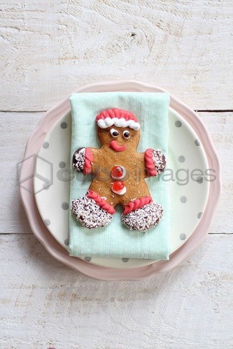 A decorated gingerbread man on a plate (seen from above)