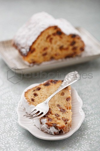 Half a stollen cake with a piece on a plate